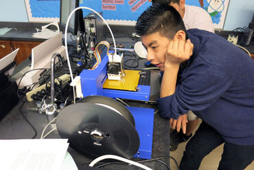 student watches a 3-D printer