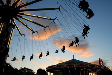 State fair patrons on swinging chairs