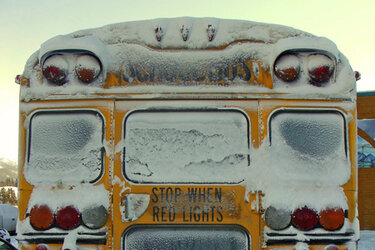Back of school bus covered in snow
