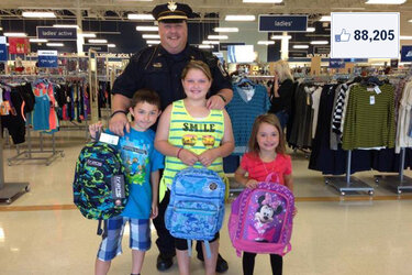 "Brimfield, Ohio, Police Chief David Oliver with children he took shopping for school clothes and supplies as part of their ""Shop with a Cop"" program."