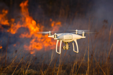 A drone flying over a wildfire.