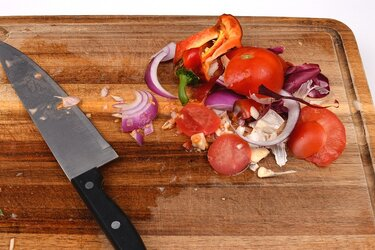 Food scraps and a knife on a cutting board.