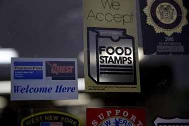 A supermarket displays stickers indicating they accept food stamps.