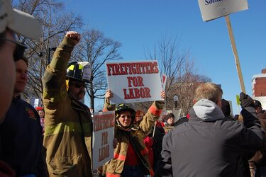 firefighters protesting and holding a sign that says firefighters for labor