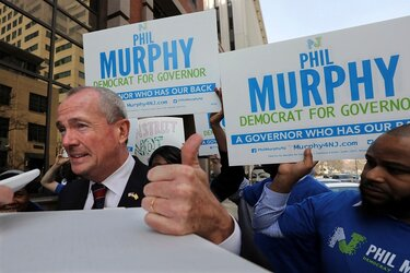 Phil Murphy and signs endorsing him for governor