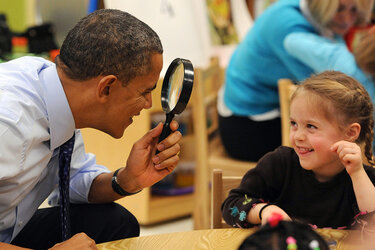 President Obama plays with a young girl at College Heights Early Childhood Learning Center in Decatur, Ga.