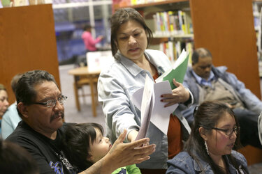 A navigator helps someone with documents during an Affordable Care Act enrollment event at a library in Fort Worth, Texas.