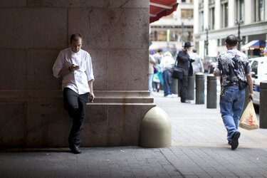 A young man taking a break from his restaurant job at Grand Central Terminal in New York City.