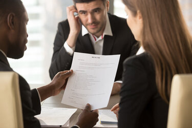 Two people interviewing another, while looking at his resume.