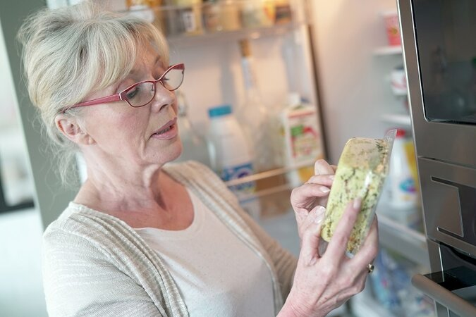 Woman checking the expiration date on food.