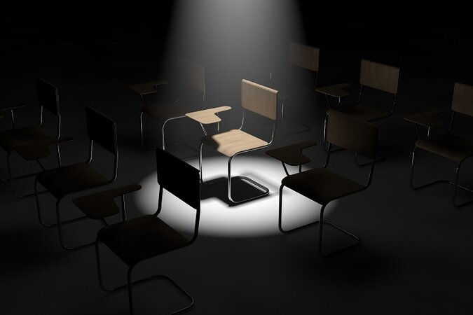 Empty chair in dark classroom.