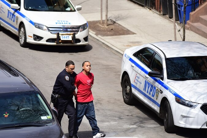 NYPD cop arresting a young black man.