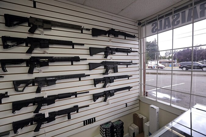 semi-automatic rifles fill a wall at a gun shop.