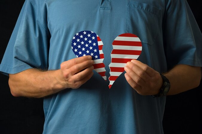 White man in button-up shirt holding a broken heart with the American flag on it,
