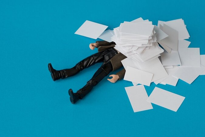 Businessman being crushed by paperwork.