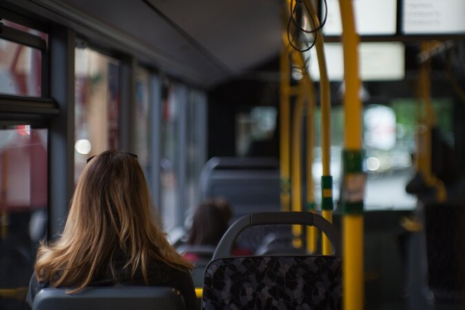 Woman sitting on a bus.