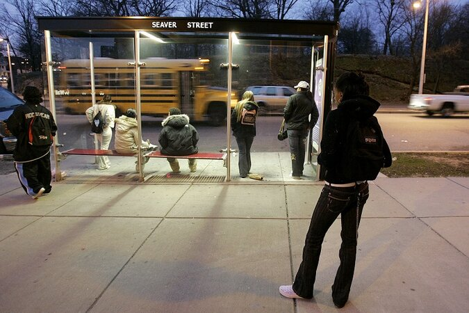 People wait at a bus stop in Boston.