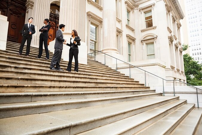 Four well dressed professionals in discussion on the exterior steps of a building with columns.