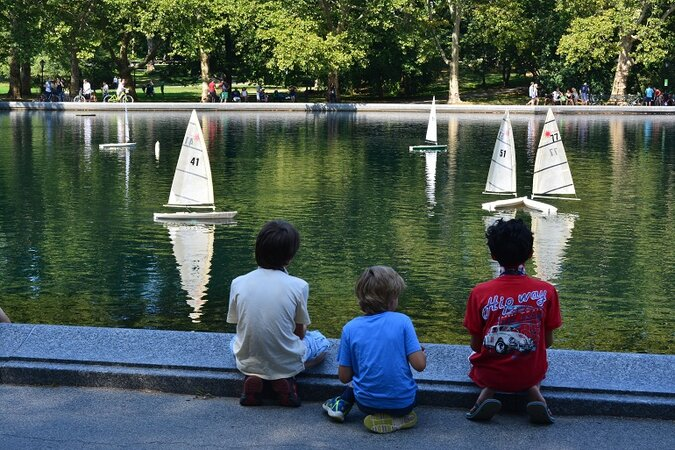 Kids sailing miniature boats in Central Park in New York City.