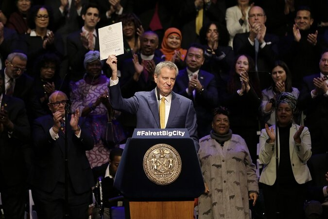 New York City Mayor Bill de Blasio holding a piece of paper up while giving a speech.