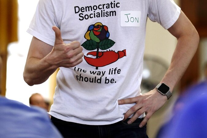 Guy wearing Democratic Socialism t-shirt and giving the thumbs up.