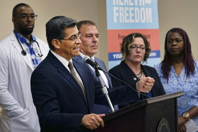 California Attorney General Xavier Becerra talking at a podium with doctors behind him.