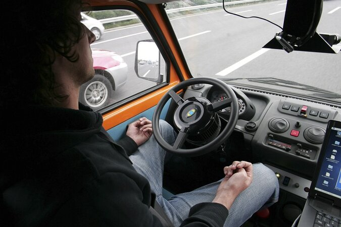 A man sitting in the driver's seat of a driverless car on the highway.