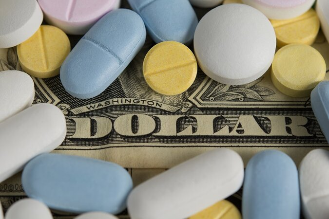 prescription drug pills covering cash