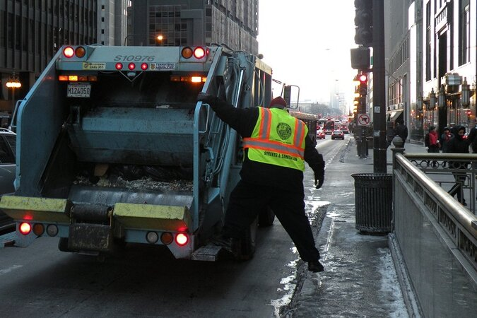 Trash collector on the back of a garbage truck in Chicago.