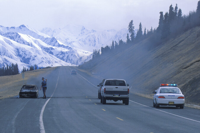 A highway patrolman next to a car on fire in Alaska.