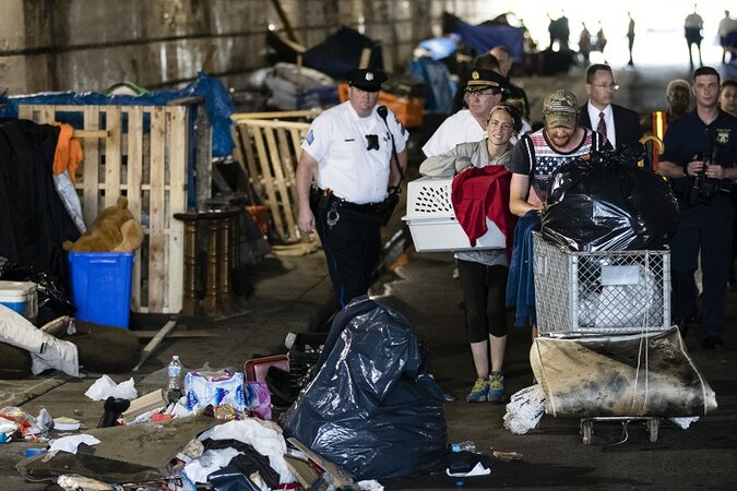 A couple, center, who were living under a bridge carry their possessions out as police move in to clear a homeless encampment in Philadelphia.