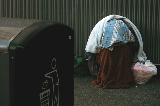 A homeless person sitting on the ground, near a trashcan