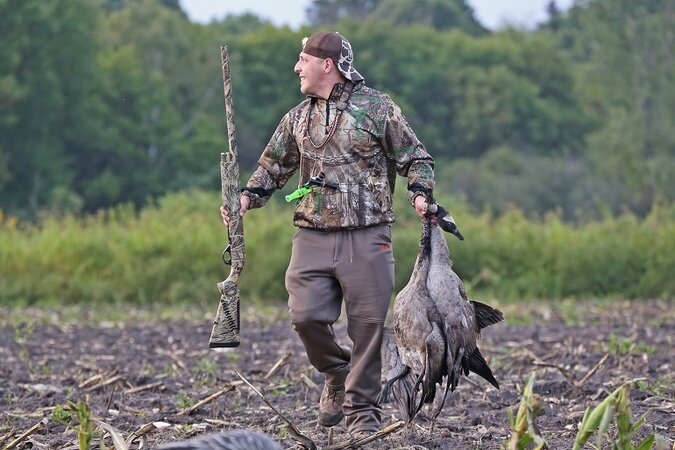 Hunter carrying a rifle and the bird he killed.