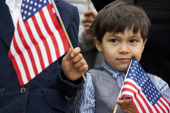 Immigrant boy waving an American flag.