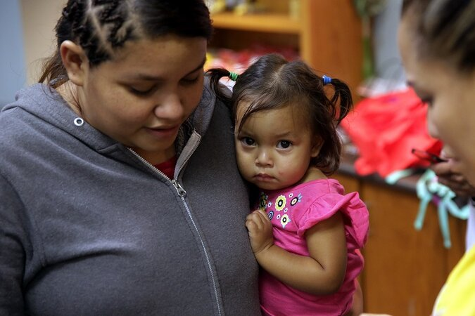 An immigrant child being held by her mother.