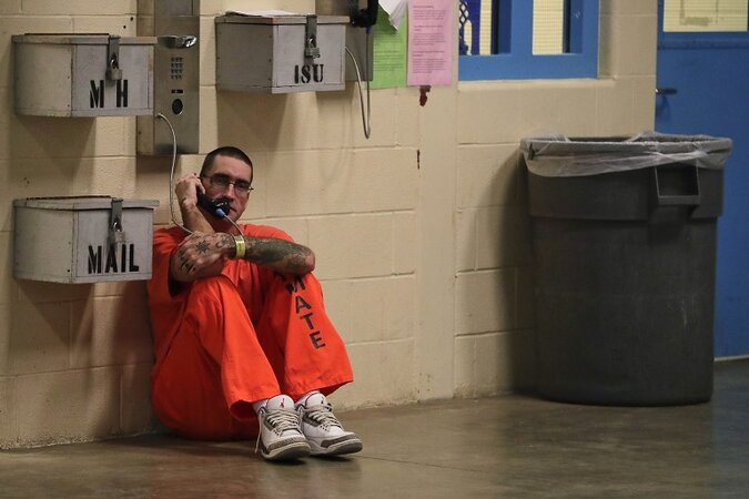 An inmate sitting on the floor making a phone call from jail.