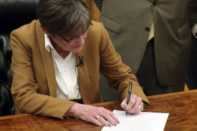 Kansas Gov. Laura Kelly signing a paper.