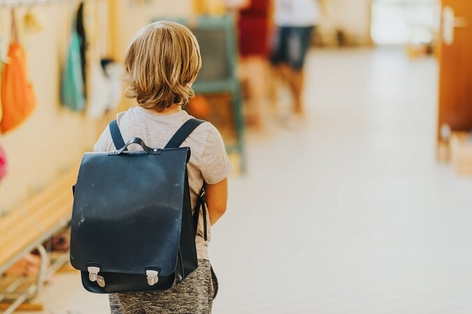 Kid walking down a school hallway with a backpack.