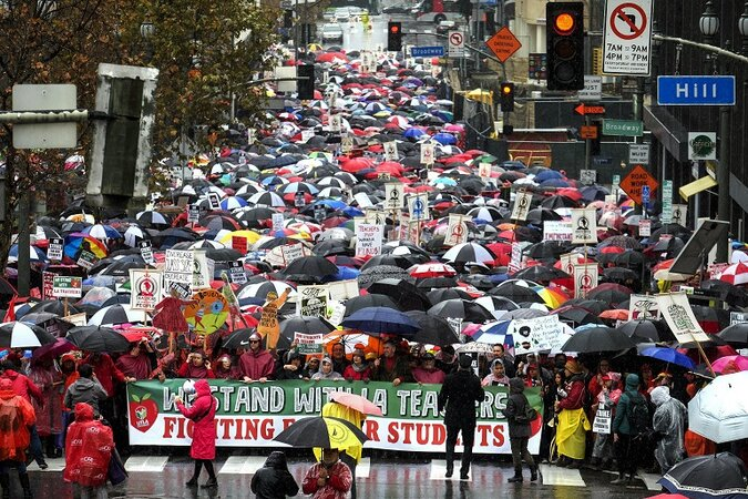Protesters holding umbrellas fill the street.