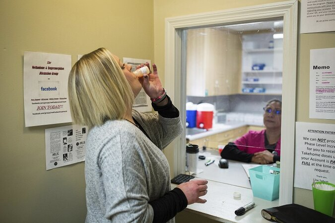 A patient takes a dose of methadone at a drug treatment clinic.