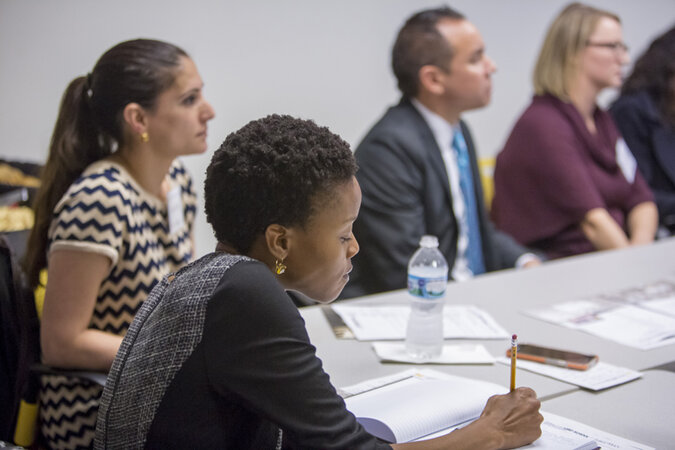 A young black woman taking notes during a meeting.