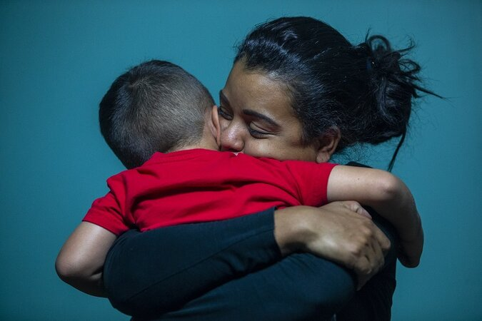 Woman hugging a small boy.