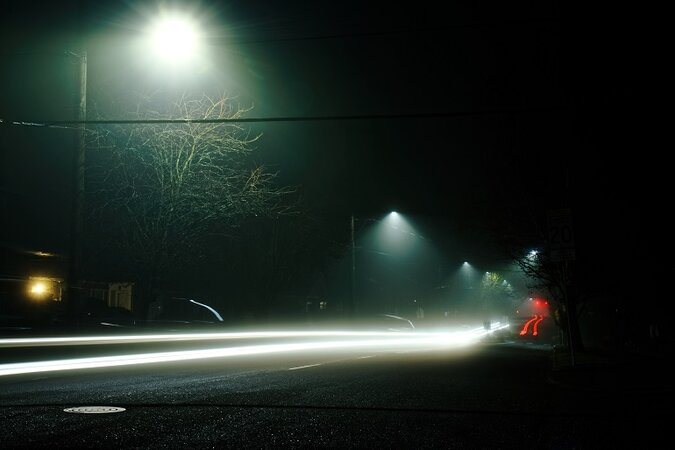 Car speeding down the road at night.