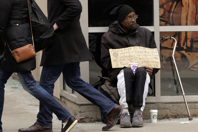 A man panhandles on the street in Chicago.