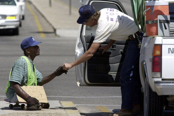 A panhandler accepts money from a passing motorist.