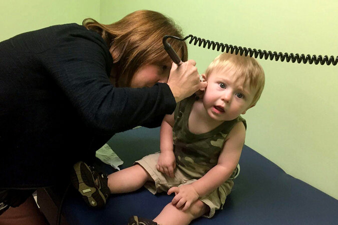 doctor looking into a baby's ear