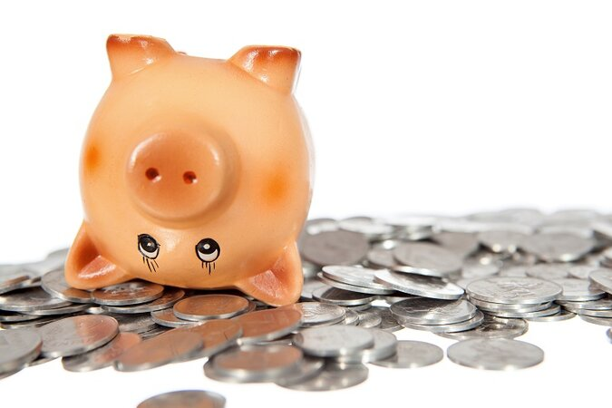 Upside down piggy bank with coins nearby.
