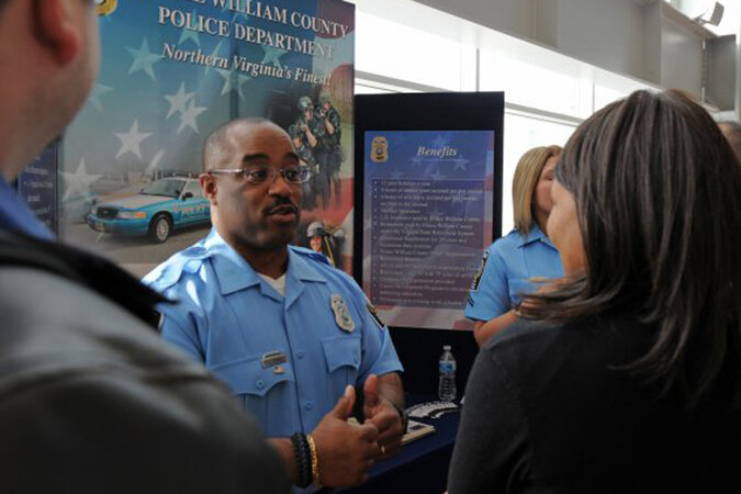 A police officer talks to people about employment opportunities with the Prince William County (Va.) police department at a job fair in Washington, D.C.