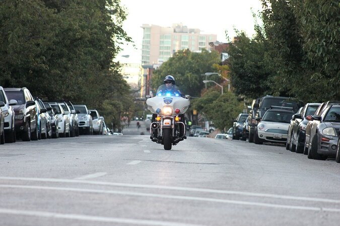 Police officer driving on a motorcycle.