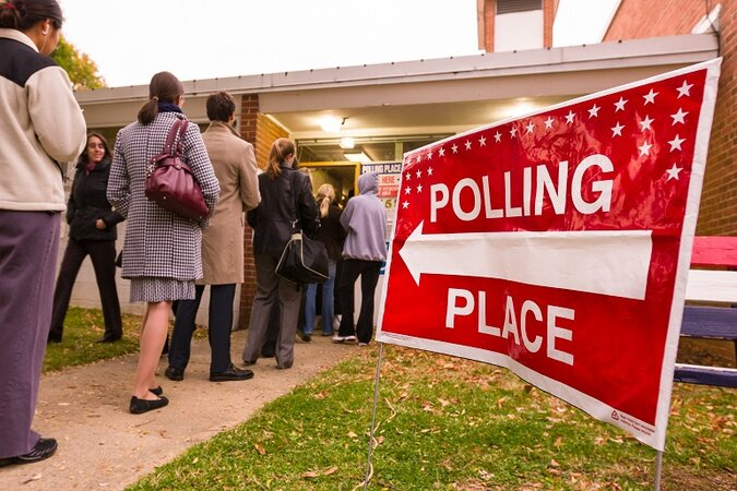 Voters stand in line at a polling station.